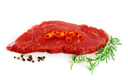 Piece of fresh raw meat with pepper, rosemary. Over white Stock Photo