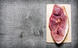 A piece of fresh raw meat on wooden Board. On the stone table. Free space for text . Top view Royalty Free Stock Photo