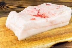 Piece of fresh, raw pork lard on wooden board, rustic background. Piece of fresh and raw pork lard on wooden board, rustic background Stock Photography