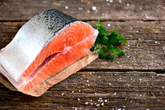 Piece of fresh raw salmon with organic parsley on an old wooden background. Food Stock Image