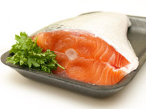 Piece of fresh raw salmon with parsley. On a tray isolated on white background Stock Photos