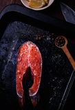 Piece of fresh raw salmon. A piece of fresh raw salmon with spices and salt on a dark background Stock Photo