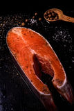 Piece of fresh raw salmon. A piece of fresh raw salmon with spices and salt on a dark background Royalty Free Stock Photos