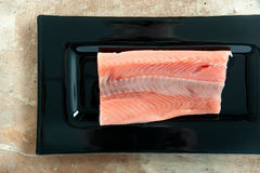 Piece of fresh salmon fillet on a dark rectangular shape dish Royalty Free Stock Photography