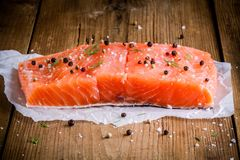 Piece of fresh salmon with pepper and sea salt. On wooden rustic background Royalty Free Stock Photos