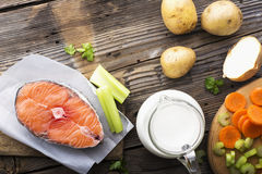 Piece of fresh sea northern salmon on a wooden background with vegetables before cooking. Top view Stock Image