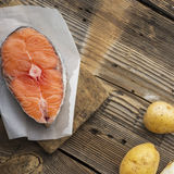 Piece of fresh sea northern salmon on a wooden background with vegetables before cooking. Top view Stock Photography