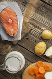 Piece of fresh sea northern salmon on a wooden background with vegetables before cooking. Top view Royalty Free Stock Images