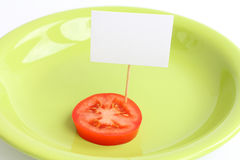 Piece of a fresh tomato with blank cardboard information tag on a plate Royalty Free Stock Photography