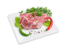 Piece of a fresh uncooked pork neck, greens and spices. Piece of a fresh uncooked pork neck, green and red chili, black and red pepper, lettuce, parsley and Stock Images