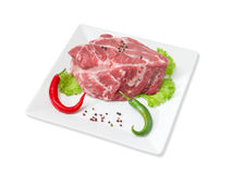 Piece of fresh uncooked pork neck, spices on square dish. Piece of a fresh uncooked pork neck, green and red chili, black and red pepper, lettuce on a white Stock Photo