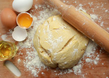 A piece of fresh yeast dough. On a wooden board are dough, eggs and sunflower oil in a glass. In yeast dough is rolling pin Royalty Free Stock Photo