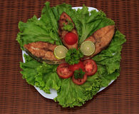 A piece of fried fish fillett served on blue glass table with lettuce, lime, tomato and herbs Stock Photos
