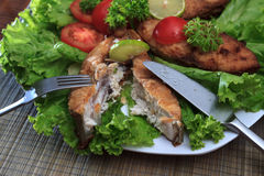 A piece of fried fish fillett served on blue glass table with lettuce, lime, tomato and herbs Royalty Free Stock Photography