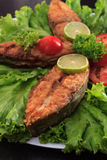 A piece of fried fish fillett served on blue glass table with lettuce, lime, tomato and herbs Royalty Free Stock Photos