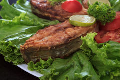 A piece of fried fish fillett served on blue glass table with lettuce, lime, tomato and herbs Stock Images