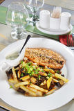 Piece of fried fish with potatoes on a served table Royalty Free Stock Photography