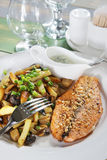 Piece of fried fish with potatoes on a table in cafe Stock Photo