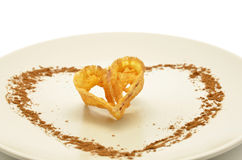 Piece of fried flower decorated with heart-shaped cinnamon Royalty Free Stock Photos