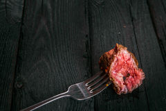 And a piece of fried meat. Grilled steak with a fork on the old board Royalty Free Stock Images