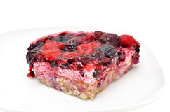 The piece of fruit cake with berries on a plate. Isolated on a white background Stock Image