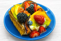 Piece of fruit cake. On a blue plate Royalty Free Stock Image