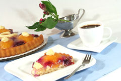 A piece of fruit cake with a cup of coffee. And Alstroemeria stock image