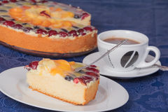 A piece of fruit cake with a cup of coffee. On blue tablecloth with pie in the background Stock Photo