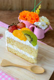 Piece of fruit cake with kiwi, strawberry and orange. With wooden spoon Royalty Free Stock Photos