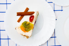 Piece of fruit cake on white plate. As table decorations cinnamon sticks and other desserts royalty free stock photography