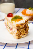 Piece of fruit cake on white plate. As table decorations cinnamon sticks and other desserts stock photography
