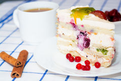 Piece of fruit cake on a white plate. Next two sticks of cinnamon, a cup of tea (coffee royalty free stock photography