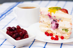Piece of fruit cake on a white plate. Next two sticks of cinnamon, a cup of tea (coffee) and a cup with berries stock photos