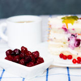 Piece of fruit cake on a white plate. Next two sticks of cinnamon, a cup of tea (coffee) and a cup with berries stock photo