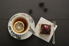 A piece of fruit and a chocolate cake and tea with lemon Royalty Free Stock Image