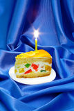 Piece of fruit jelly cake with a lighted candle. On a background of blue silk Stock Image
