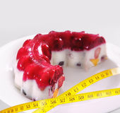 Piece of a fruit jelly cake with a measuring tape Royalty Free Stock Photography