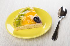 Piece of fruit pie in yellow saucer and teaspoon. On wooden table Stock Photography
