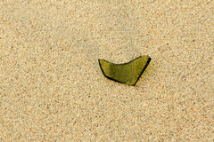 A piece of glass on sand beach Royalty Free Stock Photography
