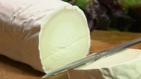 Piece of goat cheese with gray mold is cut with a knife stock video