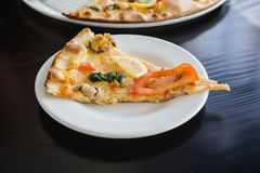 A piece of golden fragrant pizza with seafood, herbs, cheese, tomato and lemon slices on porcelain white plate Stock Photos