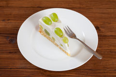 Piece of grape torte with green grapes on plate stock image