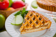 Piece of green apple pie tart dessert served next to basket of fruit. Vertical slice of apple pie tart cake dessert sweet treat Entire whole apple pie tart Royalty Free Stock Photography