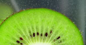 A piece of green kiwi under water with air bubbles.