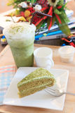 Piece of green tea cake and cool green tea ice in glass bottle a Royalty Free Stock Photography