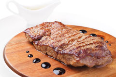 A piece of grilled meat. On a wooden board on a white background Royalty Free Stock Image