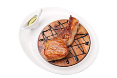 A piece of grilled meat on a wooden board. On a white background Stock Photos