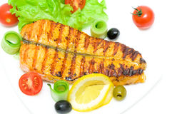 A piece of grilled salmon with vegetables and lemon on white bac Stock Image