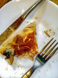 A piece of half-eaten pizza lays on a white plate next to fork and knife, top view. royalty free stock photo