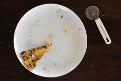 A piece of half-eaten pizza lays on a white plate next to a knif Royalty Free Stock Image